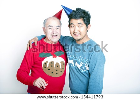 Portrait of a Senior adult man and a young Asian man wearing Christmas jumpers and party hats - stock photo