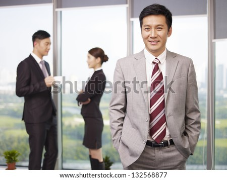 portrait of a senior business executive with his colleagues in the background. - stock photo