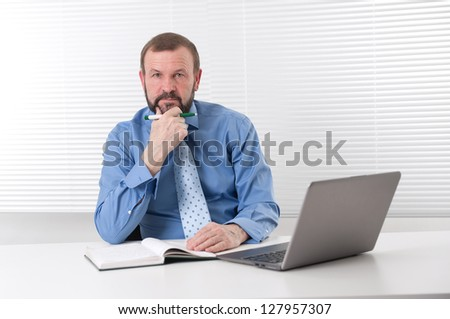 Portrait of a senior business man sitting by his laptop in the office - stock photo