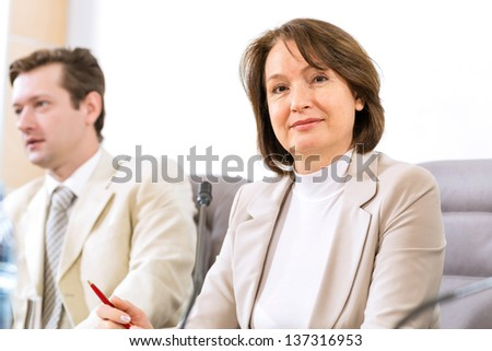 Portrait of a senior business woman at the meeting, sitting at a table on which are microphones - stock photo