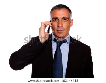 Portrait of a senior businessman looking to you using a cellphone against white background - stock photo