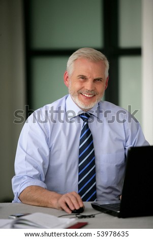 Portrait of a senior businessman with a laptop computer - stock photo