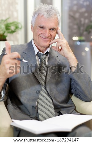 Portrait of a senior businessman with thumb up. Shallow depth of field. - stock photo