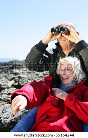 Portrait of a senior couple looking through binoculars - stock photo