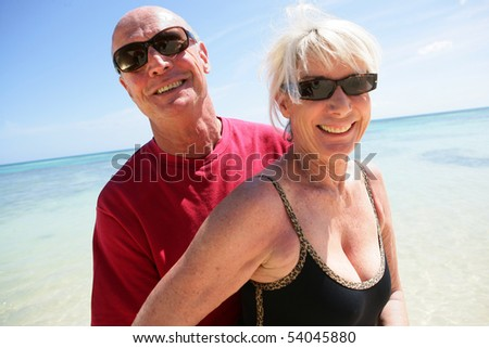 Portrait of a senior couple on the beach - stock photo