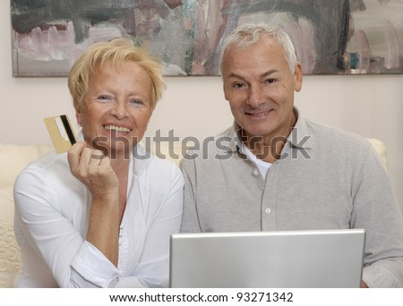 Portrait of a senior couple shopping using computer laptop. - stock photo