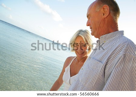 Portrait of a senior couple smiling having a walk at the seaside - stock photo