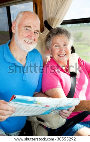 Portrait of a senior couple traveling together in their motor home. - stock photo