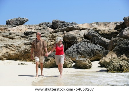 Portrait of a senior couple walking on the beach - stock photo