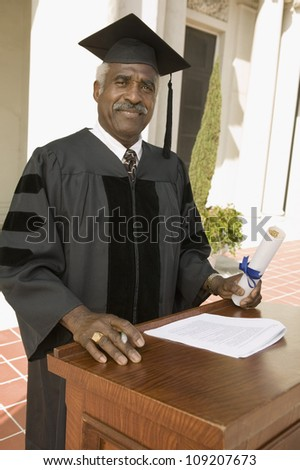 Portrait of a senior dean standing at podium on the graduation ceremony - stock photo