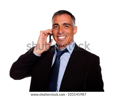 Portrait of a senior executive man smiling on mobile and wearing a black suit against white background - stock photo