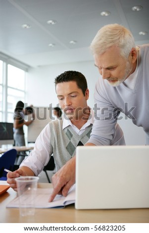 Portrait of a senior man and a young man watching a document on a desk - stock photo