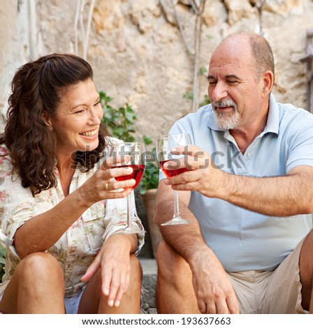 Portrait of a senior man and woman sitting on the stone steps of luxury hotel garden on holiday drinking wine and toasting in celebration, relaxing on vacation. Mature people, outdoors lifestyle. - stock photo