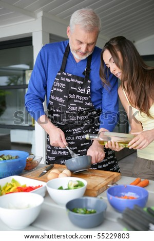 Portrait of a senior man cooking with a young woman - stock photo