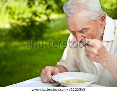Portrait of a senior man eating a soup outdoor - stock photo