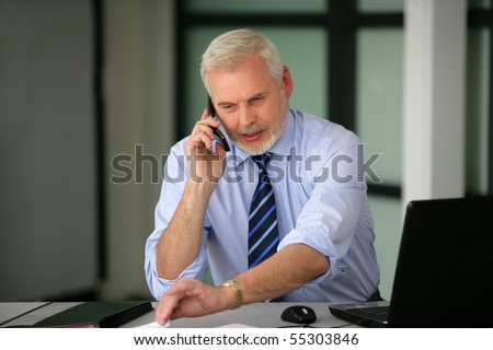 Portrait of a senior man in suit on phone - stock photo