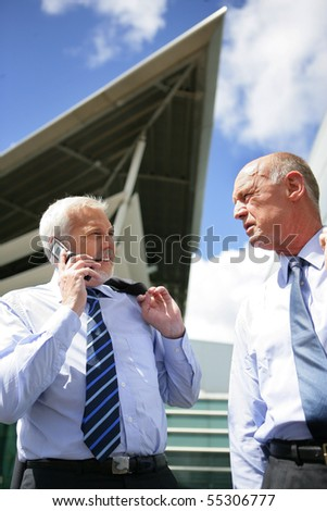 Portrait of a senior man in suit watching a senior man on phone - stock photo