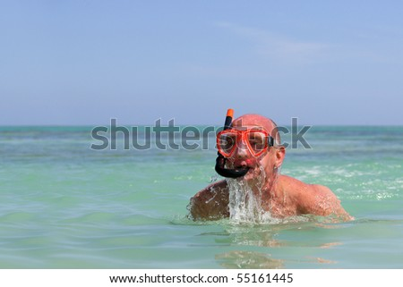 Portrait of a senior man in the sea with a snorkel and goggles - stock photo