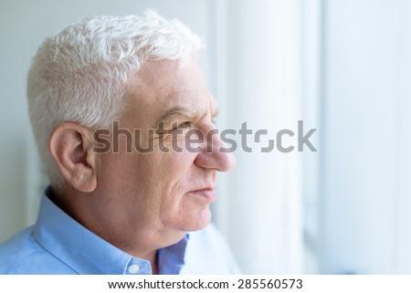 Portrait of a senior man looking through window - stock photo