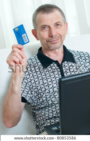 Portrait of a senior man shopping online at home - stock photo