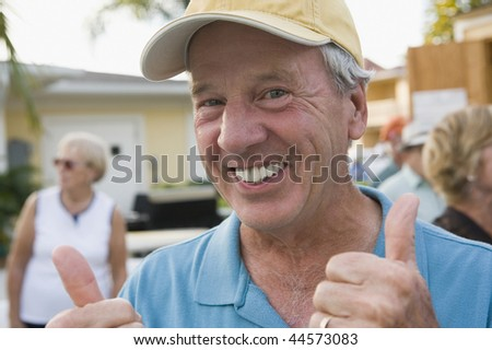 Portrait of a senior man showing a thumbs up sign and smiling - stock photo