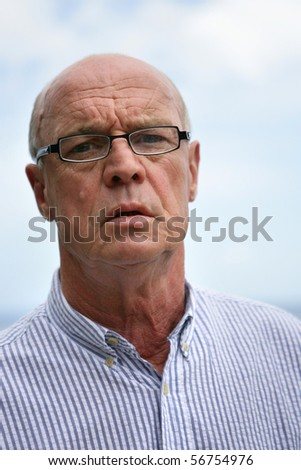 Portrait of a senior man skeptical with eyeglasses - stock photo
