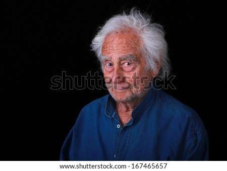 Portrait of a Senior Man with a Slight Grin on black background - stock photo