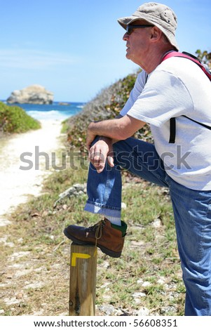 Portrait of a senior man with backpack and sunglasses looking away - stock photo