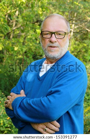 Portrait of a senior man with blue shirt and black glasses - stock photo