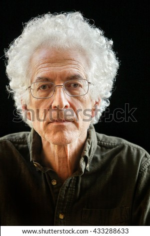 Portrait of a senior man with white curly hair against a black background. - stock photo