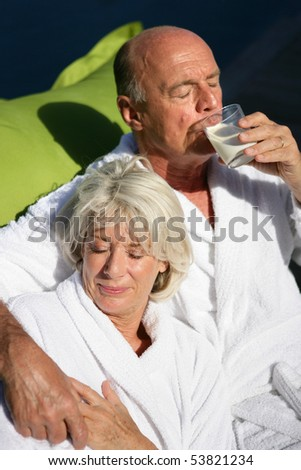Portrait of a senior woman and a senior man drinking a glass of water - stock photo