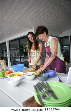 Portrait of a senior woman and a young woman cooking - stock photo