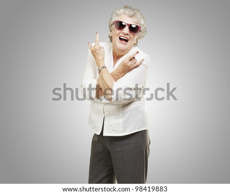 portrait of a senior woman doing a rock symbol against a grey background - stock photo