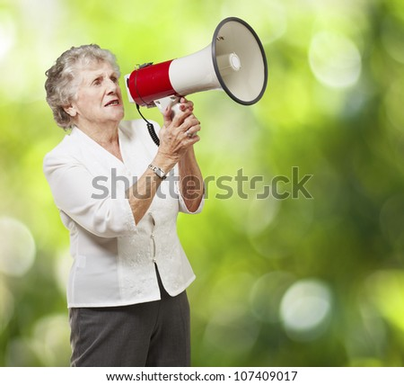 portrait of a senior woman holding a megaphone over a nature background - stock photo