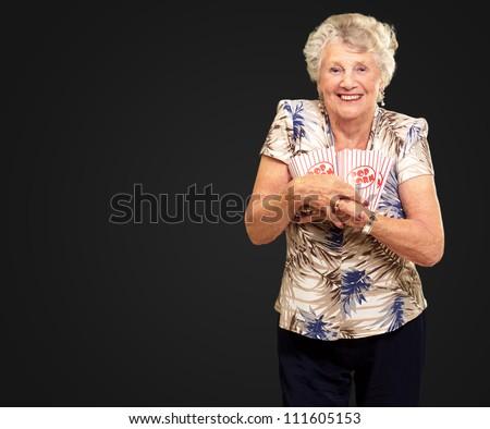 Portrait Of A Senior Woman Holding Popcorn Box On Black Background - stock photo