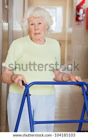 Portrait of a senior woman in hospital using Zimmer frame - stock photo