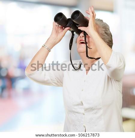portrait of a senior woman looking through binoculars indoor - stock photo