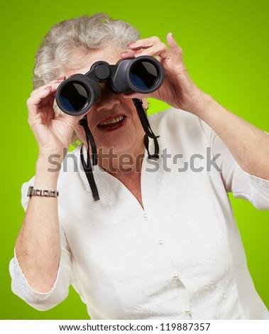 Portrait of a senior woman looking through binoculars on green background - stock photo