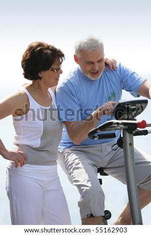 Portrait of a senior woman next to a senior man making exercise bike - stock photo