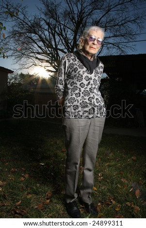 Portrait of a senior woman outdoors, thinking - stock photo