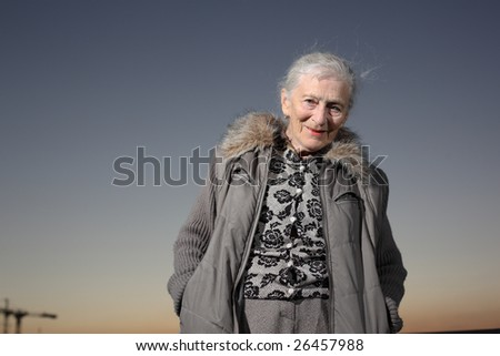 Portrait of a senior woman over sunset sky - stock photo