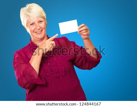 Portrait Of A Senior Woman Pointing To The Blank Card On Blue Background - stock photo