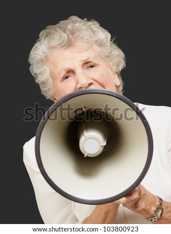 portrait of a senior woman screaming with a megaphone over a black background - stock photo