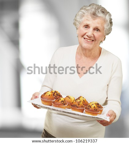 portrait of a senior woman showing homemade muffins indoor - stock photo