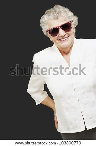 portrait of a senior woman standing and wearing sunglasses over a black background - stock photo