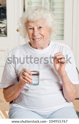 Portrait of a senior woman taking a pill with a glass of water - stock photo