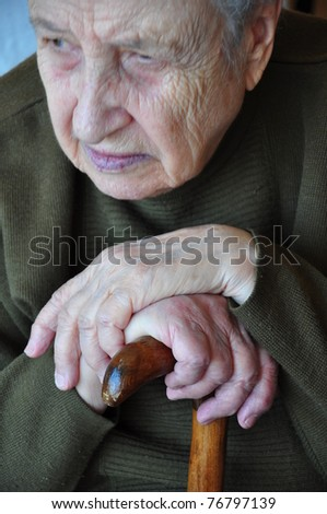 Portrait of a senior woman thinking hands on her cane - stock photo