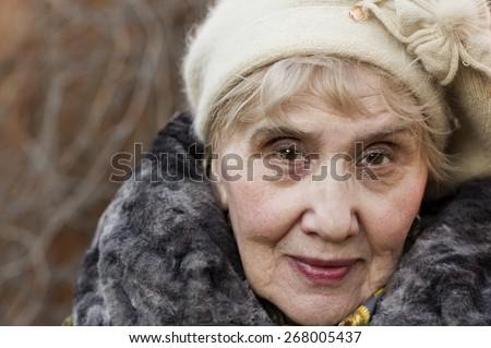 Portrait of a senior woman wearing hat, outdoor portrait - stock photo