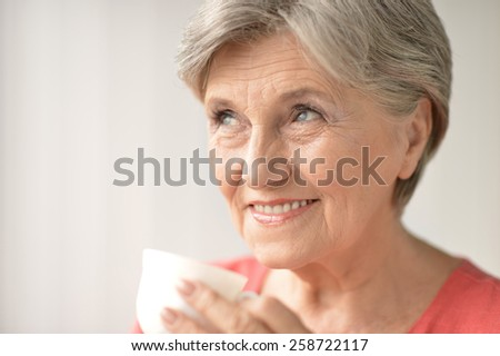 Portrait of a senior woman with cup at home - stock photo