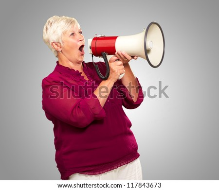 Portrait Of A Senior Woman With Megaphone On Gray Background - stock photo
